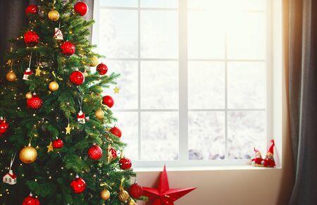 Arbre intérieur de Noël avec des cadeaux près de la fenêtre à la maison Banque d'images