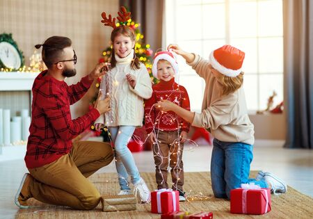 happy family decorate Christmas tree, parents play with children with garlands at home Фото со стока