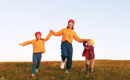 happy family mother and children running in autumn nature at sunset Stockfoto