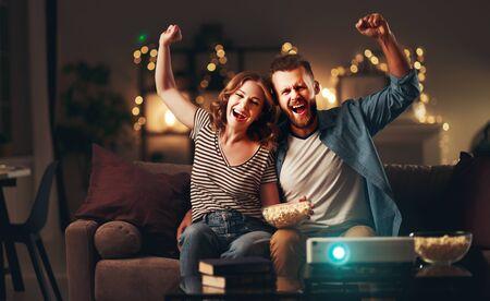Familienpaar vor dem Fernsehprojektor zu Hause auf dem Sofa