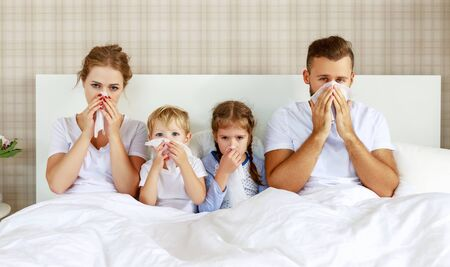 colds and viral diseases. family with runny nose and fever in bed at home