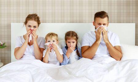 rhumes et maladies virales. famille avec écoulement nasal et fièvre au lit à la maison