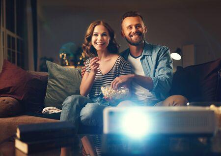 Familienpaar vor dem Fernsehprojektor zu Hause auf dem Sofa watching