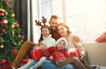 genitori e figli felici della famiglia aprono i regali la mattina di Natale