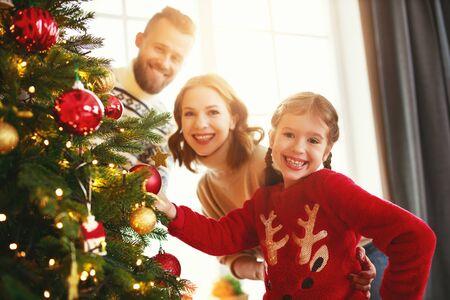 Feliz madre de familia, padre e hija infantil decoran el árbol de Navidad en casa