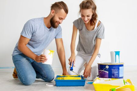 young happy couple is repairing and painting the wall at home Foto de archivo