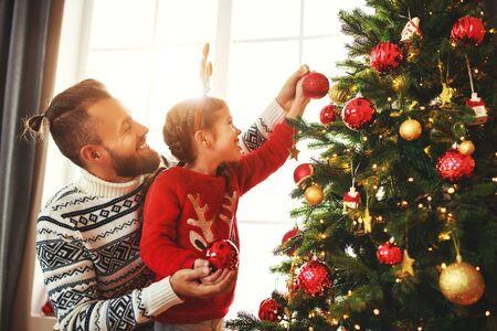 padre de familia feliz y niña decoraron un árbol de navidad