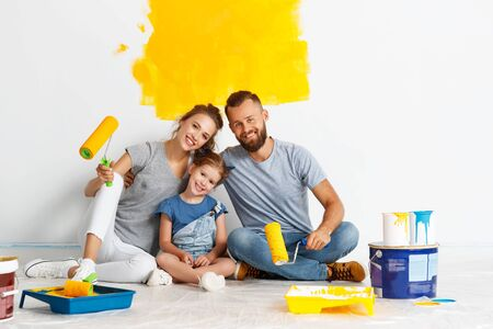 Repair in the apartment. Happy family mother, father and child daughter paints the wall with paint