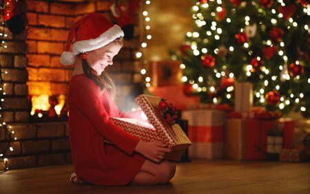 gelukkig lachend kindmeisje met een magisch cadeau dat op kerstavond voor de kerstboom zit Stockfoto