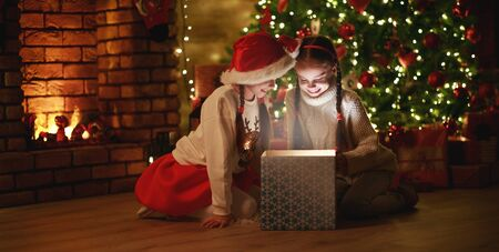 Merry Christmas!happy children with magic gift at evening home near  Christmas tree and fireplace