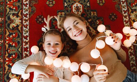 happy family mother and child daughter with Christmas lights garland