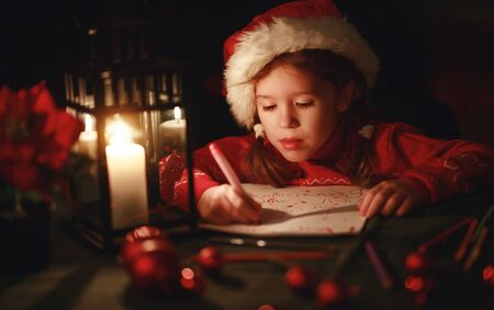 happy child girl writing letter santa home near the Christmas tree