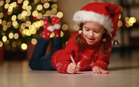 happy child girl writing letter santa home near the Christmas tree  스톡 콘텐츠