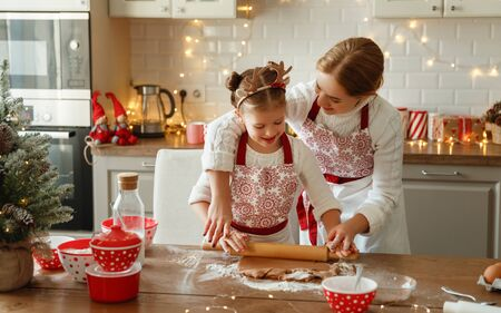 happy funny mother and child daughter bake christmas cookies
