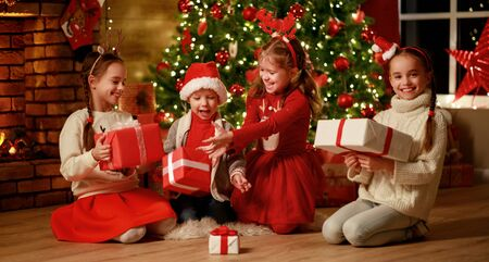 Merry Christmas!happy children with   gifts at evening home near  Christmas tree and fireplace