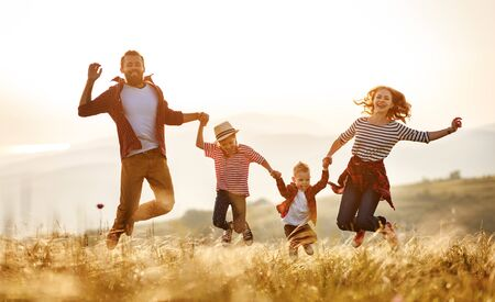 Happy family: mother, father, children son and  daughter jumping on nature  on sunset