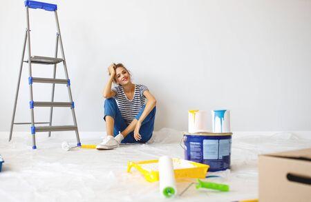 Naprawa w mieszkaniu. Szczęśliwa młoda kobieta maluje ścianę żółtą farbą