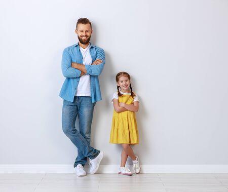 concepto de familia. el padre y el niño con una hija cerca de una pared vacía. Foto de archivo