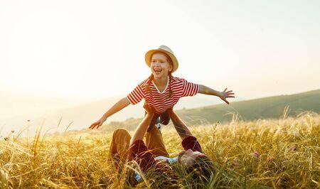 Fête des pères. Heureux père de famille et fille enfant jouant et riant sur la nature au coucher du soleil