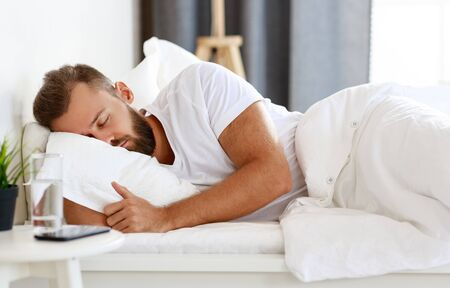 young man sleeping in bed in bedroom in the morning Stok Fotoğraf