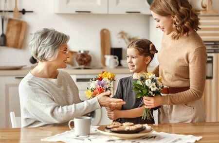 mothers day! three generations of a loving family mother, grandmother and daughter congratulate on the holiday, give flowers