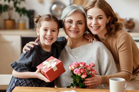 mother's day! three generations of a loving family mother, grandmother and daughter congratulate on the holiday, give flowers Stock Photo