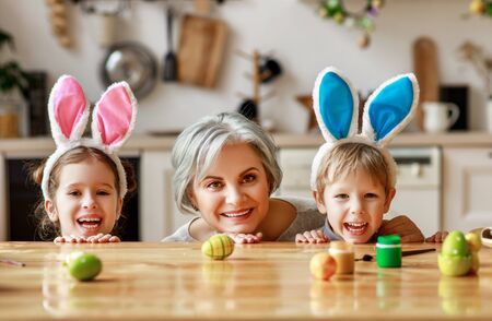 Happy easter! family grandmother and children grandchildren paint eggs for the holiday