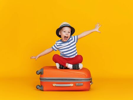 Happy little boy with outstretched arms and open mouth sitting crossed legged on luggage and pretending to fly against yellow background