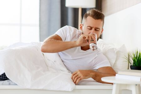 young healthy man drinking water in morning at window Stockfoto
