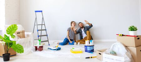 Young couple woman and boyfriend pointing away  while sitting near white wall and planning room interior during renovation in new apartment