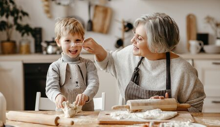 Senior woman and little boy while rolling soft dough during pastry preparation in cozy kitchen at home Foto de archivo