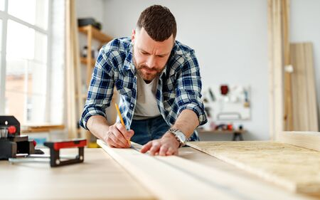 young male carpenter working in a workshop Stock fotó