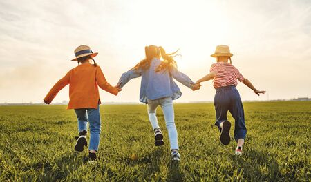 Unrecognizable cheerful little girls in casual clothes having fun and running back in together in green field at sunset while enjoying summer holidays in countryside Stock Photo