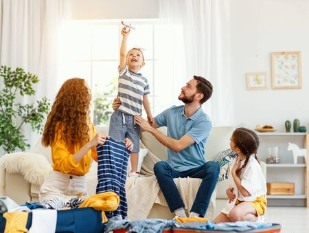Happy family of parents and boy with girl packing suitcases for vacation trip while playing on sofa in living room