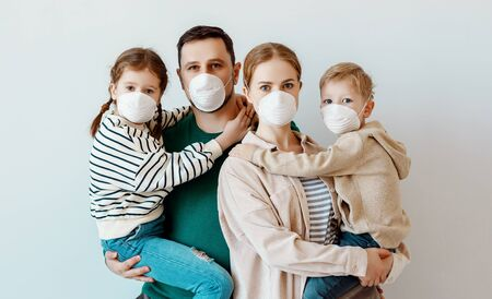 Parents and kids in medical masks looking at camera while standing against gray wall during contagious coronavirus epidemic