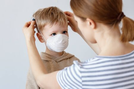 Adult woman putting on medical mask on little boy during coronavirus outbreak against gray background