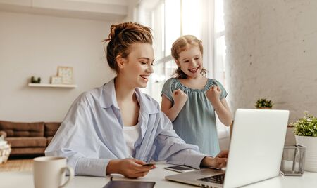 Low angle of happy small daughter with arms raised rejoicing while smiling mother in casual clothes focusing on screen and using laptop for online shopping in light modern apartment Banque d'images - 144124863