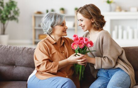 Cheerful young female hugging happy aged mother and giving bouquet of tulips while congratulating on mother day at home