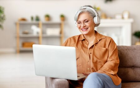 Happy senior lady in casual clothes and headphones smiling and watching movie on laptop while sitting on sofa at home