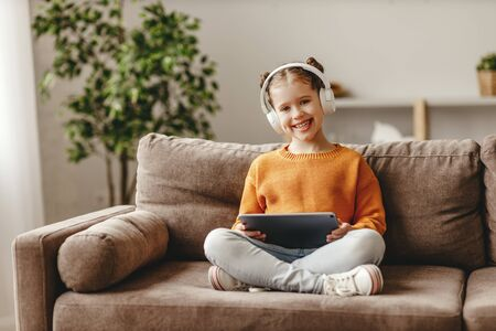 Full body cheerful girl in casual clothes and headphones smiling and playing game on tablet while sitting on soft couch at home Stockfoto