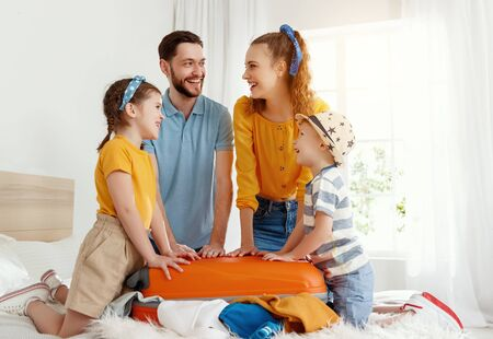 Laughing kids and parents gathering on bed closing suitcase together while getting packed for vacation looking at each other with smiles Stockfoto