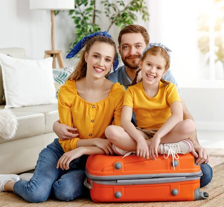 Smiling couple with charming little girl sitting on suitcase in living room looking happily at camera ready for summer trip