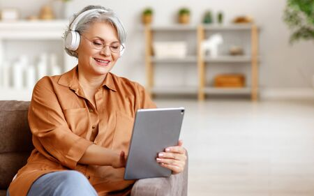Happy elderly female in headphones smiling and browsing social media on tablet while sitting on sofa and listening to music at home