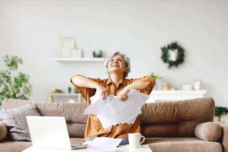 Excited senior lady smiling and throwing documents up after finish of freelance project while sitting on couch at home
