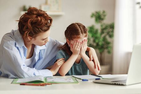 Kind mother embracing and comforting small crying daughter having difficulties with homework while sitting at table and doing exercise in copybook in cozy apartment 免版税图像