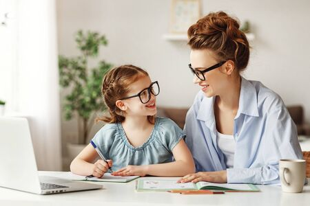 Pleased mother and small daughter in glasses and casual clothes looking at each other and smiling while sitting at table and school supplies and laptop and doing home task together in light contemporary apartment