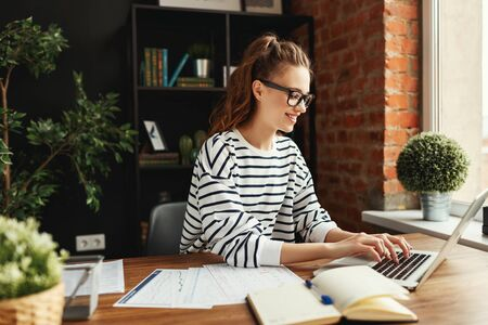 Smiling young woman in glasses and casual clothes focusing on screen and typing on laptop while sitting at wooden desk with papers and notepad in loft office with green potted plants 스톡 콘텐츠