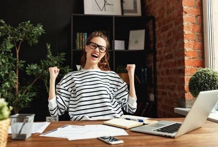 Happy young lady with eyes closed and arms raised rejoicing in success while sitting at wooden table with notepad and laptop in loft office among green potted houseplants