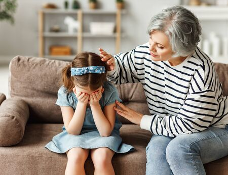 Elderly woman in casual clothes embracing and comforting crying girl while sitting on sofa at home together