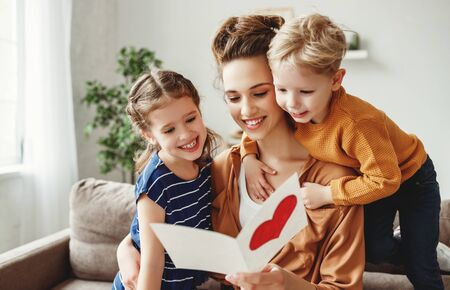 Joyful young mother and little children sitting on sofa and embracing while reading wishes and congratulations with holiday in presented postcard at home